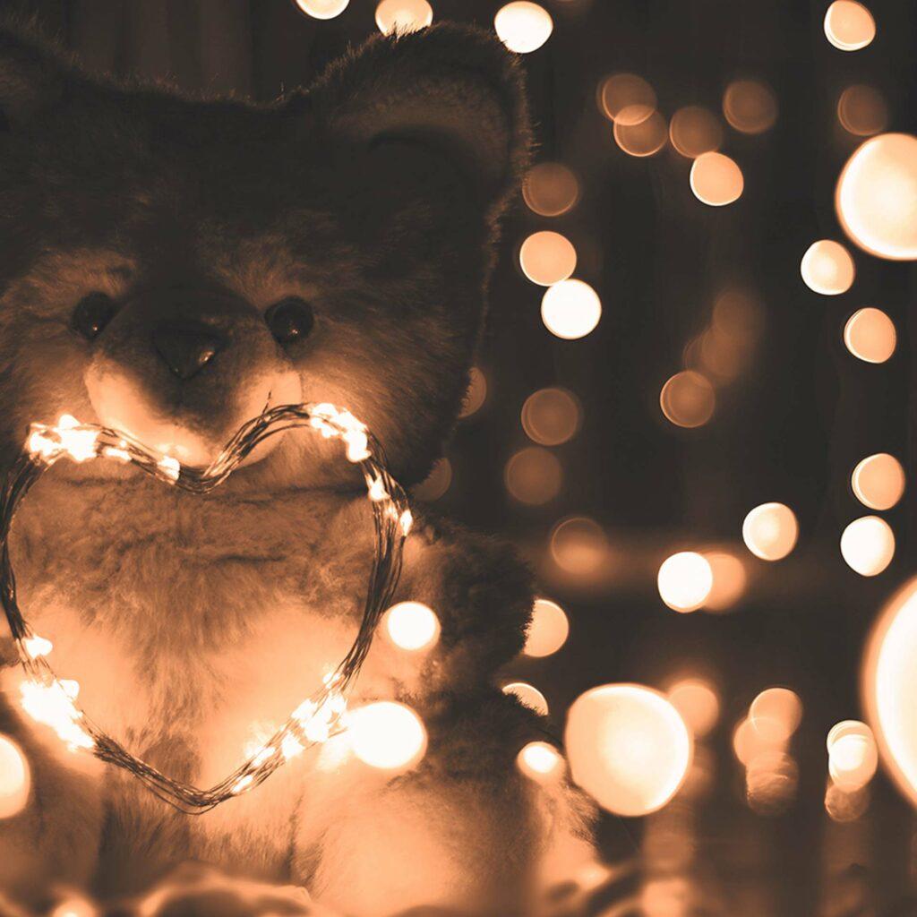 Ours en peluche éclairé d'une guirlande de lumière, dans une ambiance mélancolique évoquant le deuil d'un bébé.