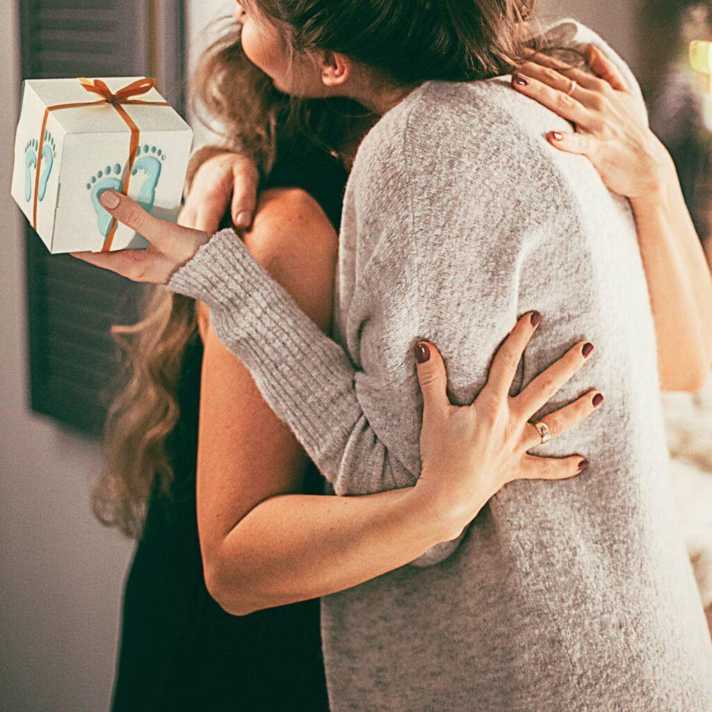 Femme enceinte qui embrasse et remercie son amie pour le cadeau offert à son futur bébé.
